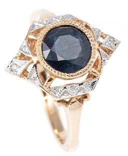Sale 9124 - Lot 473 - A DECO STYLE SAPPHIRE AND DIAMOND RING; centring a millegrain set round cut dark blue sapphire of approx. 1.41ct in a pierced surrou...