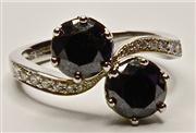 Sale 8036A - Lot 325 - A MOISSANITTE AND DIAMOND RING; set with two 6.6mm round black moissanitres to bypass shoulders set with 16 round brilliant cut diam...