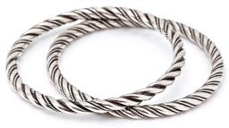Sale 9132 - Lot 327 - TWO SILVER TWIST BANGLES; 5mm wide full round bangles twisted with twisted wire work (1 has losses), internal diam. 62mm, total wt....