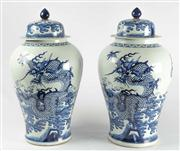 Sale 8444A - Lot 25 - A pair of large Chinese blue and white lidded vases decorated with dragons over crested waves, height 61cm with qianlong marks to base