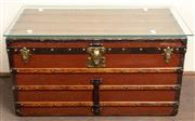 Sale 8871H - Lot 85 - A vintage French Louis Vuitton steamer trunk / coffee table circa 1930 with removable glass top, the trunk covered in dark orange Vu...