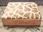 Sale 8308A - Lot 215 - An interesting and rare giraffe hide and leather upholstered ottoman, raised on industrial castors, H 33 D 70 W 76cm