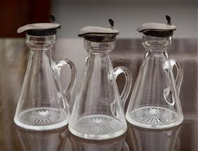 Sale 9195H - Lot 31 - Three hallmarked sterling silver topped oil bottles, Height 11.5cm