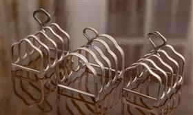 Sale 9195H - Lot 36 - A Hardy Brothers sterling silver toast rack, together with a pair of plated examples