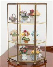 Sale 8515A - Lot 14 - A miniature glass and glass hexagonal cabinet displaying a quantity of Flowers of the Year ceramic baskets of flowers, H of cabinet...
