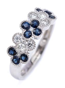 Sale 9246J - Lot 336 - A 18CT WHITE GOLD SAPPHIRE AND DIAMOND RING; set across to the top with quatrefoil clusters set with round cut blue sapphires and ro...
