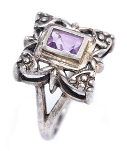 Sale 9194 - Lot 329 - A STERLING SILVER GEMSTONE RING; in the Wager style centring a baguette cut amethyst to a foliate surround on split shoulders, size...