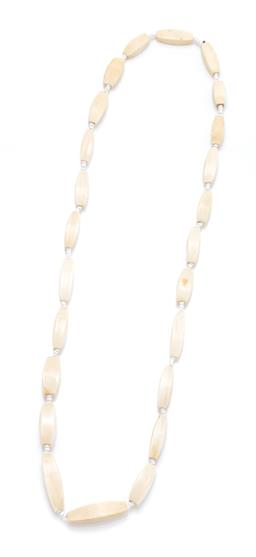Sale 9253J - Lot 332 - A VINTAGE IVORY BEAD NECKLACE; graduated 8 x 22.5 - 9.5 x 33mm beads to white paste bead spacers, length 64cm.
