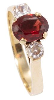 Sale 8965 - Lot 311 - A 14CT GOLD GEMSET RING; set with an oval cut garnet and 2 round cut zirconias, size O, wt. 3.14g.