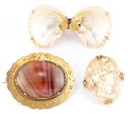 Sale 8915 - Lot 356 - THREE ANTIQUE GOLD FRAMED STONE BROOCHES; 18ct gold engraved brooch set with a banded agate, (4 x 3cm), wt. 9.73g, a shell cameo por...