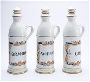 Sale 8528A - Lot 8 - A set of three hand painted Porcelain de Paris decanters, for Whisky, Brandy & Gin, total H 30cm