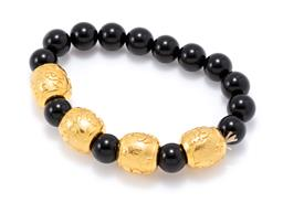 Sale 9177 - Lot 374 - A 24CT GOLD AND ONYX BRACELET; 14 x 10mm round onyx beads, between 4 x 24ct gold cloud design pattern beads, 15 x 14mm, each beads m...