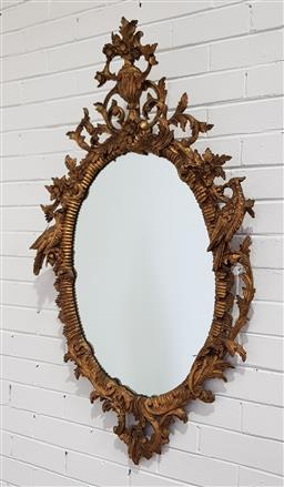 Sale 9162 - Lot 1027 - Chippendale style gilt oval mirror, the rocaille frame with leaf scrolls, surmounted by an urn and flanked by ho-ho birds (broken sc...
