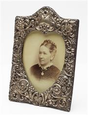 Sale 9080W - Lot 4 - A Sterling silver photograph frame with hearl shape aperture and vacant scroll cartouche above image.19 x 13.5cm Birmingham marks.