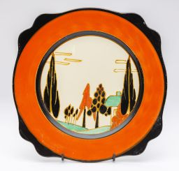 Sale 9150J - Lot 30 - A rare Fantasque house amidst trees painted plate by Clarice Cliff decorated with a deep red and black border of shaped outline C: 1...