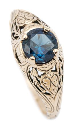 Sale 9083 - Lot 410 - AN EDWARDIAN STYLE 9CT GOLD SOLITAIRE SAPPHIRE RING; centring a blue round cut sapphire of approx. 0.75ct on carved gallery and shou...