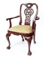 Sale 9044J - Lot 20 - A superior ornately hand carved mahogany elbow chair C: 1900s. The chair similar to a 1760s Chippendale armchair with a carved cre...