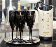 Sale 8709 - Lot 1056 - A set of six Moet champagne flutes in black glass on an ep waiters tray marked Savoy together with a Moet bottle cooler