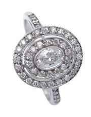 Sale 9080J - Lot 58 - An 18ct white gold and diamond target ring, set to the centre with an oval cut diamond framed by an oval band of 14 diamonds, the ou...