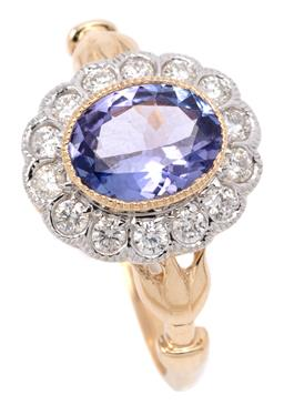Sale 9132 - Lot 387 - A TANZANITE AND DIAMOND CLUSTER RING; centring an oval cut tanzanite of approx. 1.10ct to scalloped surround set with 14 round brill...