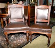 Sale 8015A - Lot 76 - A set of fourteen leather upholstered Edwardian ornately carved mahogany dining chairs on casters including two carvers
