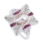 Sale 8879 - Lot 377 - A DECO STYLE 18CT WHITE GOLD DIAMOND AND RUBY RING; centring an oval full rose cut diamond of approx. 0.49ct in collet setting highl...