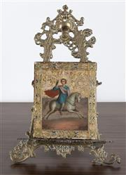 Sale 8486A - Lot 5 - A brass easel in the Rococo taste, H 36cm, displaying an Icon depicting a saint on horseback.