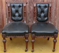 Sale 8934H - Lot 32 - A pair of carved oak and button back upholstered library chairs with carved detail and castors to front legs,