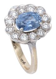 Sale 8982 - Lot 399 - AN 18CT WHITE GOLD SAPPHIRE AND DIAMOND CLUSTER RING; centring an approx. 1.7ct oval cut pastel blue sapphire (abraded) to scalloped...