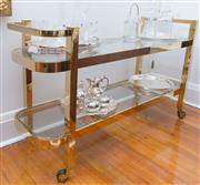 Sale 8530A - Lot 28 - An art deco style serving cart in gold plated stainless steel and glass top on casters, W 140 x D 46 x H 78cm