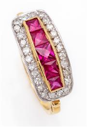 Sale 9044J - Lot 51 - A ruby, diamond and 18ct gold ring, the centre being 5 calibre cut rubies of graduating size framed by 26 diamonds above a scrolled ...