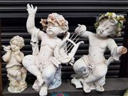 Sale 8925 - Lot 1056 - A harp playing cupid together with a cherub and bird and one other with broken hand (3)
