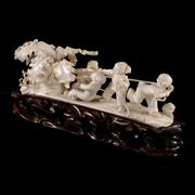 Sale 8000 - Lot 267 - A Chinese Republic Period carved ivory figure group of children pulling a giant radish with carved timber stand.