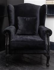 Sale 8761A - Lot 19 - A black velvet upholstered and studded wingback armchair, Height of back 105cm, W x 83cm