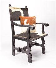 Sale 8473A - Lot 19 - An unusual cowhide upholstered armchair in the Tudor style, the carved pine timber structure painted black with pinned stretcher to...