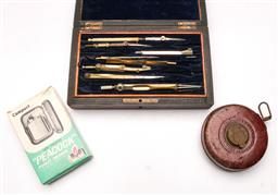 Sale 9119 - Lot 47 - A cased protractor set, measuring tape and pocket warmer