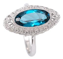 Sale 9132 - Lot 444 - A BELLE EPOCH STYLE TOPAZ AND DIAMOND RING; centre millgrain set with an oval cut London blue topaz of approx. 3.30ct to surround of...