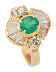 Sale 9083 - Lot 541 - AN EMERALD AND DIAMOND CLUSTER RING; centring an approx. 0.75ct modified oval cut emerald (chip) above a surround of 6 graduated tap...