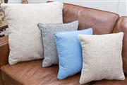 Sale 8530A - Lot 25 - A collection of new scatter cushions on leather chesterfield