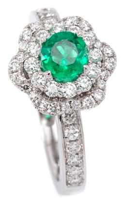 Sale 9132 - Lot 411 - AN 18CT WHITE GOLD EMERALD AND DIAMOND CLUSTER RING; centring a round cut emerald of approx. 0.50ct, surrounded by a halo above a sc...