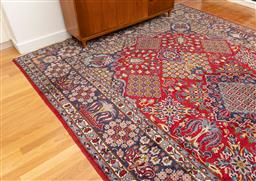 Sale 9239H - Lot 28 - A hand knotted wool Persian rug with repeating floral motif on red ground, 440x 300cm.