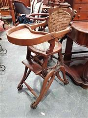Sale 8925 - Lot 1093 - A vintage timber and cane adjustable childs high chair on iron wheels