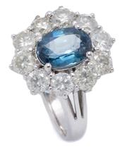 Sale 8999 - Lot 385 - AN 18CT WHITE GOLD SAPPHIRE AND DIAMOND CLUSTER RING; centring a blue oval cut sapphire of approx. 2.4ct surrounded by 10 round bril...