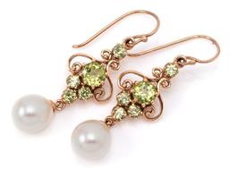 Sale 9132 - Lot 384 - A PAIR OF NOUVEAU STYLE PERIDOT AND PEARL DROP EARRINGS; 9ct scroll drops set with round cut peridots suspending 8mm long drop shape...