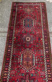 Sale 8891H - Lot 8 - A Persian runner of repeated medallion design against a red ground, 490 x 83cm.