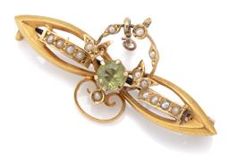 Sale 9107J - Lot 355 - AN AUSTRALIAN ANTIQUE 15CT GOLD GEMSET BROOCH; centring a round cut peridot to leaf and wreath scroll surround, set with seed pearls...