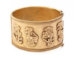 Sale 9107J - Lot 346 - A GILT AZTEC DESIGN CUFF BANGLE; 38mm wide gold tone hinged bangle with Aztec motifs and plaited pattern with twin safety clip closu...