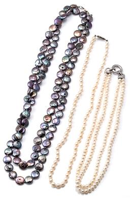 Sale 9124 - Lot 580 - THREE CULTURED FRESHWATER PEARL NECKLACES; 11.5mm round black button pearls with peacock overtones to silver parrot clasp, length 13...