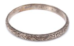 Sale 9182 - Lot 322 - A VINTAGE MOROCCAN SILVER BANGLE; 7.6mm wide bangle with scroll and flower design, with hallmarks for Marrakech, diam. 63mm, wt. 44....