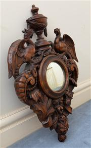 Sale 8815A - Lot 12 - A continental oak convex mirror the frame with elaborate carving of gryphons urns, swags and acanthus detail, Height 70cm, Width 45cm,